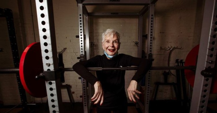 Elderly lady with weight training bar